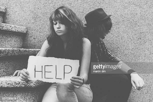 Unappy couple holding help wanted sign at the street