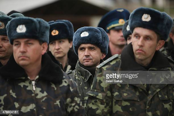 Unarmed Ukrainian troops listen to their commander speak before they marched to confront soldiers under Russian command occupying the nearby Belbek...