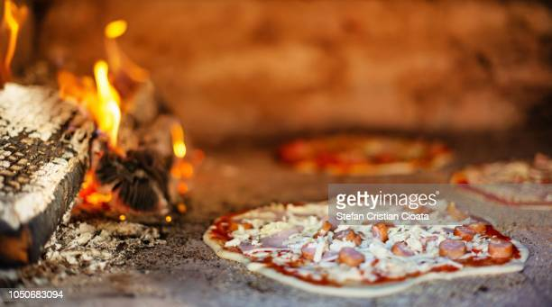 unbaked pizza in a bread wood-fired oven - südeuropa stock-fotos und bilder