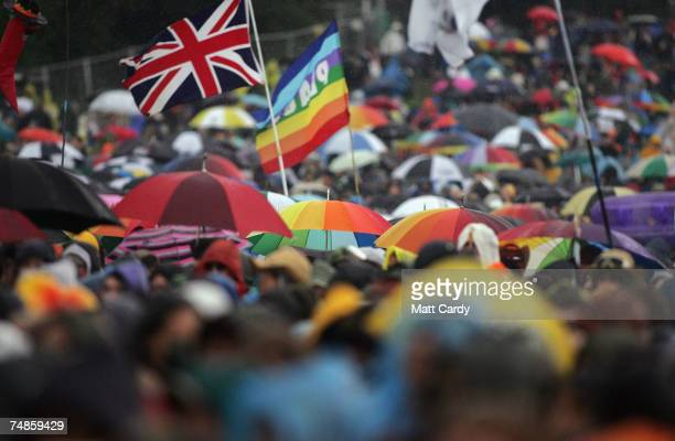 Unbrellas and flags wave in the rain as Amy Winehouse performs on the Pyramid Stage at Worthy Farm Pilton near Glastonbury on June 22 2007 in...