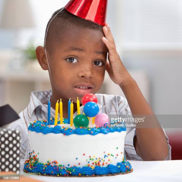 Uncertain Black boy standing near birthday cake