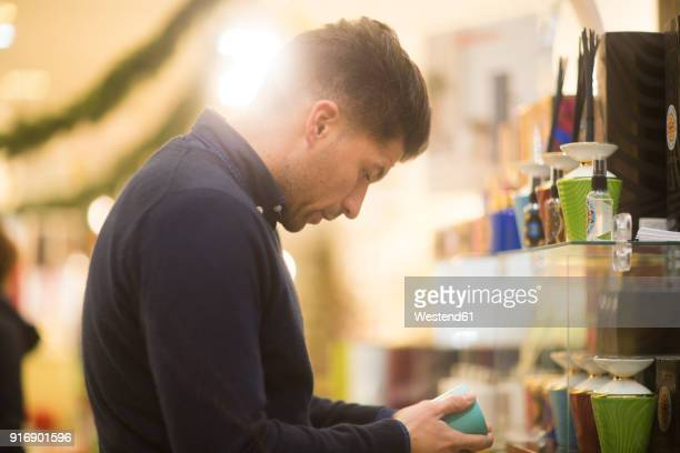Uncertain man looking for Christmas present in a shop