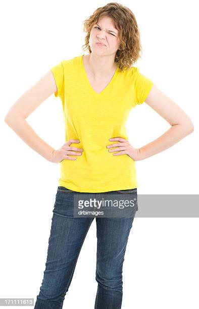 uncertain young woman standing with hands on hips - v neck stock photos and pictures
