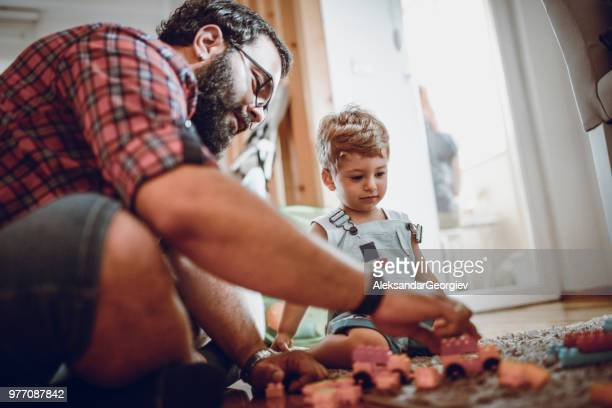 uncle and baby boy combining different lego bricks together - uncle stock photos and pictures