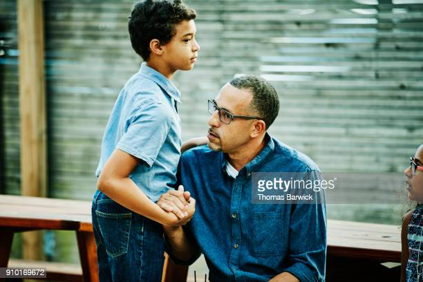 uncle and nephew greeting each other before outdoor family dinner party - nephew stock pictures, royalty-free photos & images