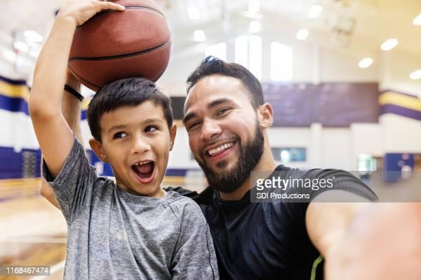 oom en neef nemen silly selfie met basketbal in gym - head coach stockfoto's en -beelden