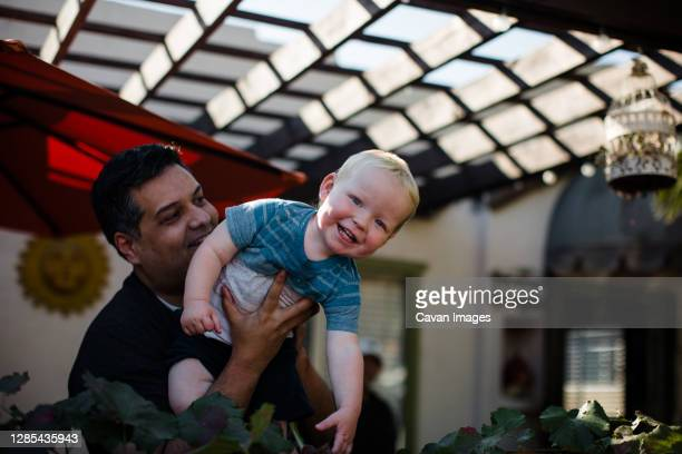uncle holding nephew in front yard in san diego - nephew stock pictures, royalty-free photos & images
