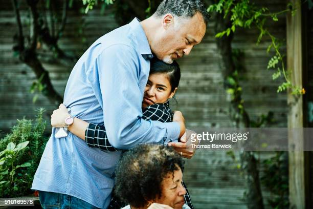 uncle hugging niece before family dinner on summer evening - uncle stock photos and pictures