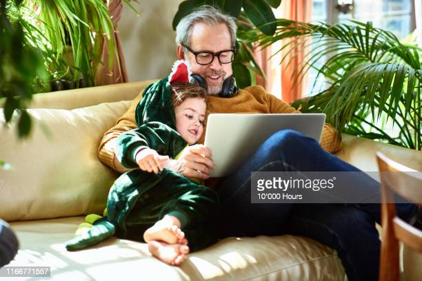 uncle playing game on laptop with girl in dinosaur outfit - genderblend stock pictures, royalty-free photos & images