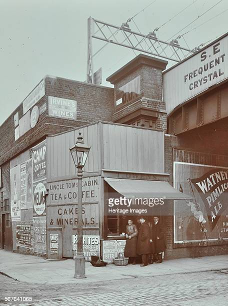Uncle Tom's Cabin tea stall 394b Wandsworth Road London 1909 Customers stand at a corner tea and coffee stall under the railway bridge To the left...
