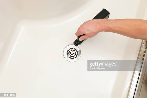 unclogging shower with liquid drain cleaner - drain cleaner stock photos and pictures