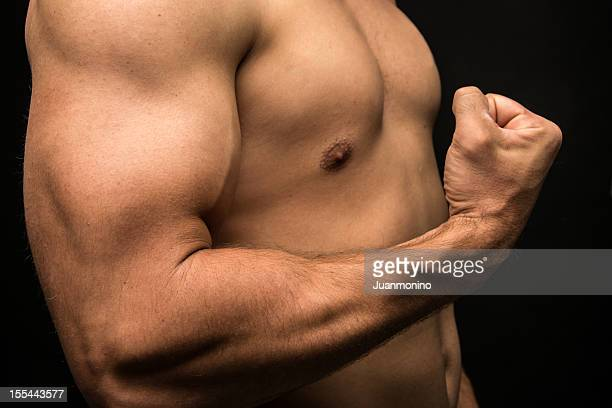 Unclothed side shot of muscled male clenching fist