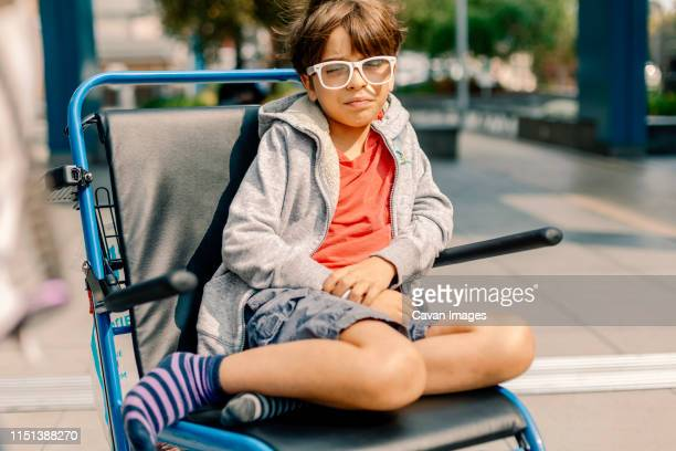 uncomfortable boy in wheel chair leaving the hospital - outpatient care stockfoto's en -beelden