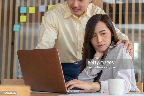 uncomfortable businesswoman looking away while sitting by colleague in office - sexual harassment stock pictures, royalty-free photos & images
