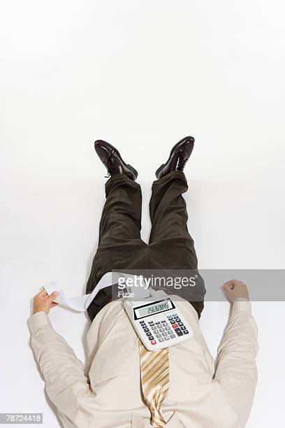Unconscious Businessman with Adding Machine