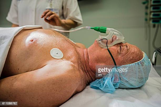 Unconscious man lying in a hospital bed with oxygen mask