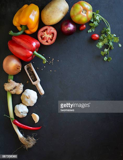 Uncooked fresh vegetables, herbs and spices on moody black background.
