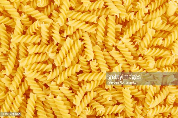 uncooked fusilli pasta background - spiral stock pictures, royalty-free photos & images