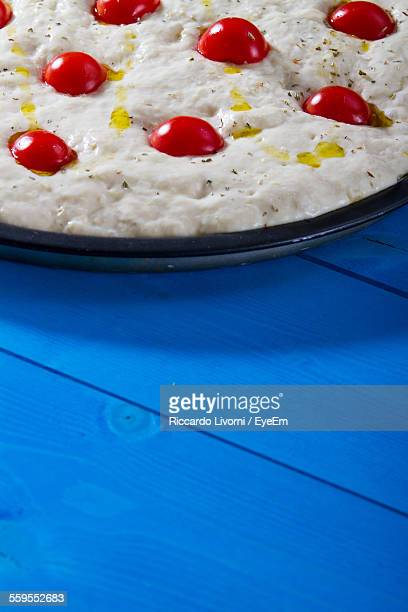 Uncooked Pizza With Cherry Tomato Toppings On Blue Table