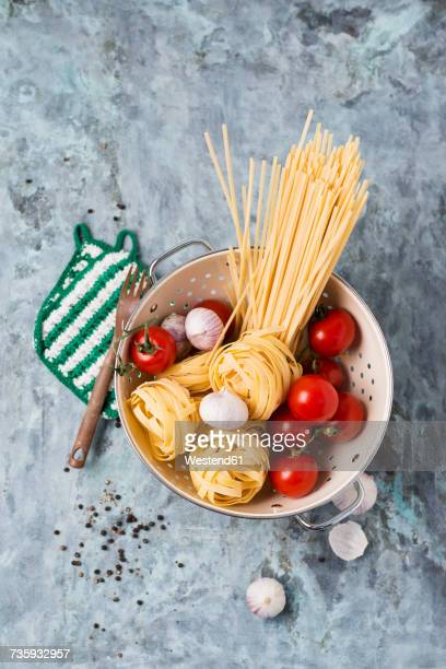 Uncooked Taglatelle, Spaghetti, tomatoes ans garlic bulbs in colander