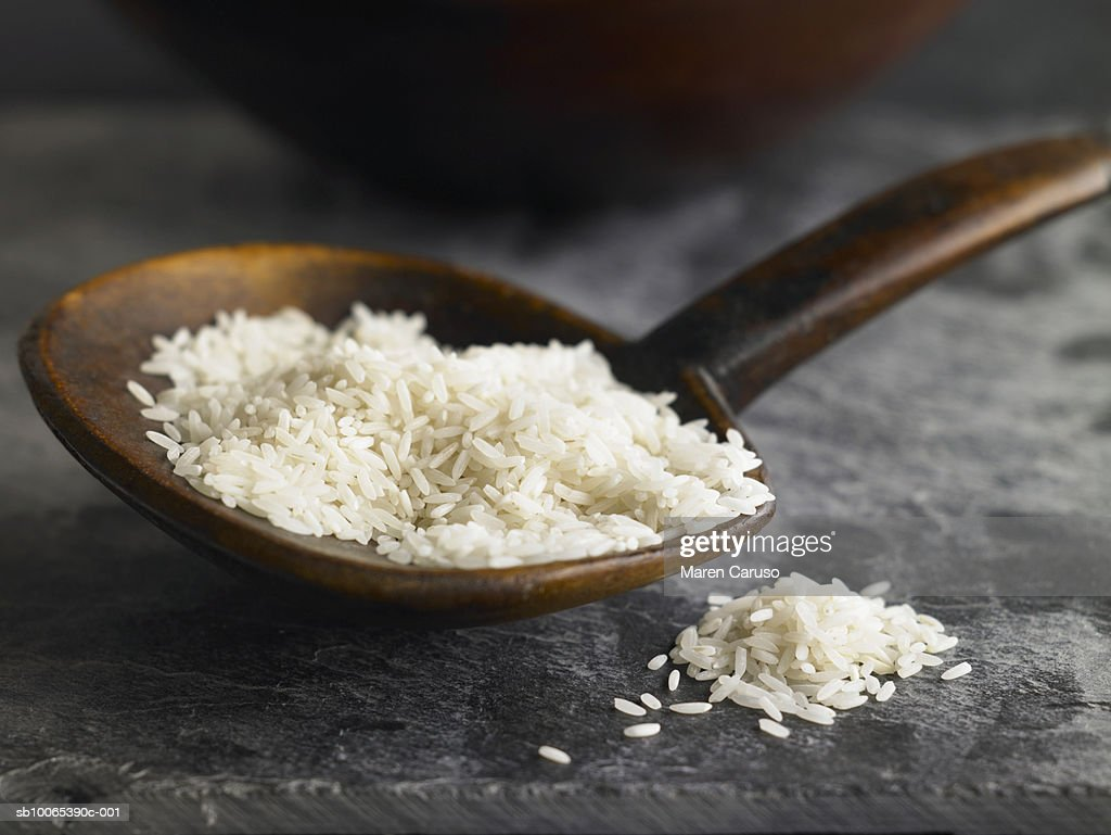 Uncooked white rice in wooden spoon on stone surface, close-up : Foto stock