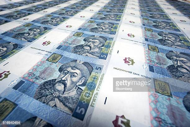 Uncut sheets of five hryvnia banknotes depicting Bohdan Khmelnytsky sit on display in this arranged photograph at the headquarters of the National...