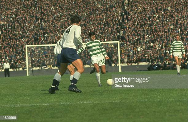 Bertie Auld of Celtic kicks the ball away as Alan Mullery of Tottenham Hotspur watches during a Friendly match at Celtic Park in Glasgow, Scotland. \...