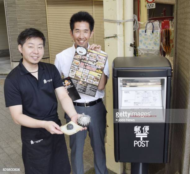 Undated photo shows officials of a mall in Yawatahama in Ehime Prefecture western Japan standing next to a black postbox and holding a blackcolored...