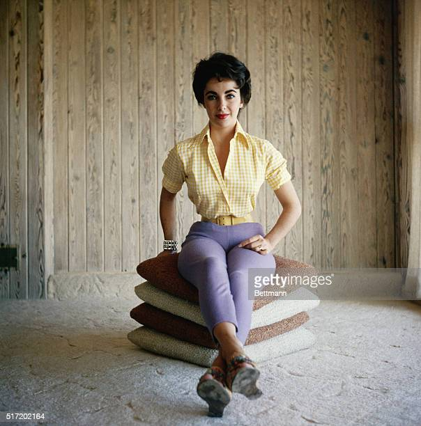 Undated photograph of actress Elizabeth Taylor, sitting on a stack of pillows, wearing purple pants and a yellow shirt, and smiling.