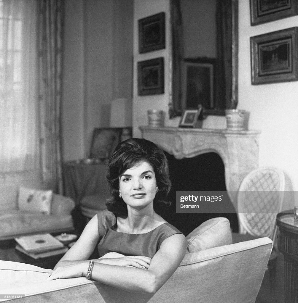 Undated photograph of Jacqueline Kennedy, seated, leaning on the back of a couch, circa 1960's.