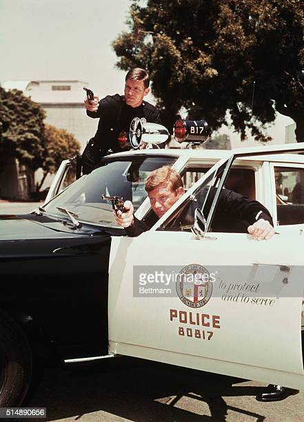 Undated TV still from Adam 12 showing Kent McCord as Officer James A Reed and Martin Milner as Officer Peter J Malloy at their squad car and pointing...