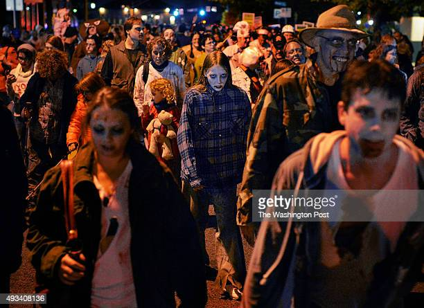 Undead citizens make their way along Sligo avenue during the annual Zombie Walk on October 2013 in Silver Spring MD