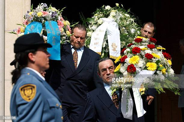 Undentified people carry flowers in front of UN security staff after the funeral ceremony for UN special envoy to Iraq Sergio Vieira de Mello at...