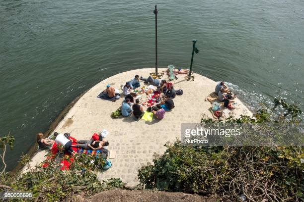 Under a blazing sun tourists and Parisians go out to reclaim the banks of the Seine in Paris on April 22 2018