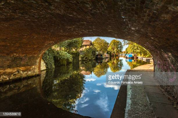 under a bridge on regent's canal next to victoria park, with house, boats and trees reflected on the water - ビクトリア公園 ストックフォトと画像