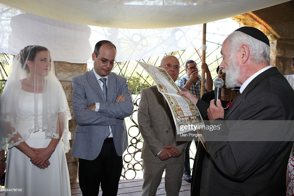 Under a Chuppa (or canopy) at an Orthodox Jewish wedding a Rabbi reads  sc 1 st  Getty Images & Jewish Wedding Ceremony Pictures | Getty Images