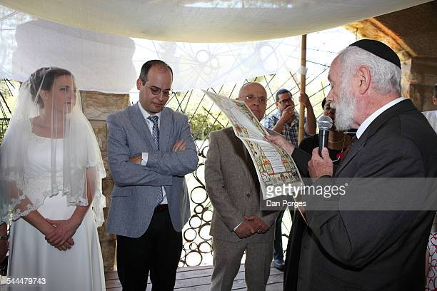 Under a Chuppa at an Orthodox Jewish wedding a Rabbi reads the marriage contract to the bride and groom Jerusalem Israel August 29 2014