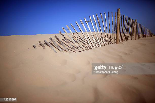 Under a cloudless sky a wooden fence is taken over by a sand dune at Formby point beach on April 19 2011 in Formby United Kingdom Weather forecasters...