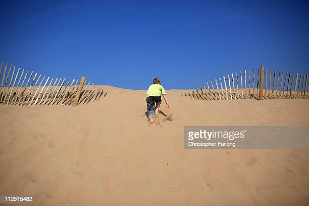 Under a cloudless sky a young boy climbs a sand dune at Formby point beach on April 19 2011 in Formby United Kingdom Weather forecasters are...