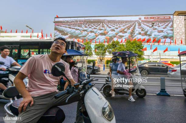 Under a giant screen on Renmin Road in Fuyang City, a man on a motorbike looks up to watch a live TV broadcast of the Centenary Celebration of the...