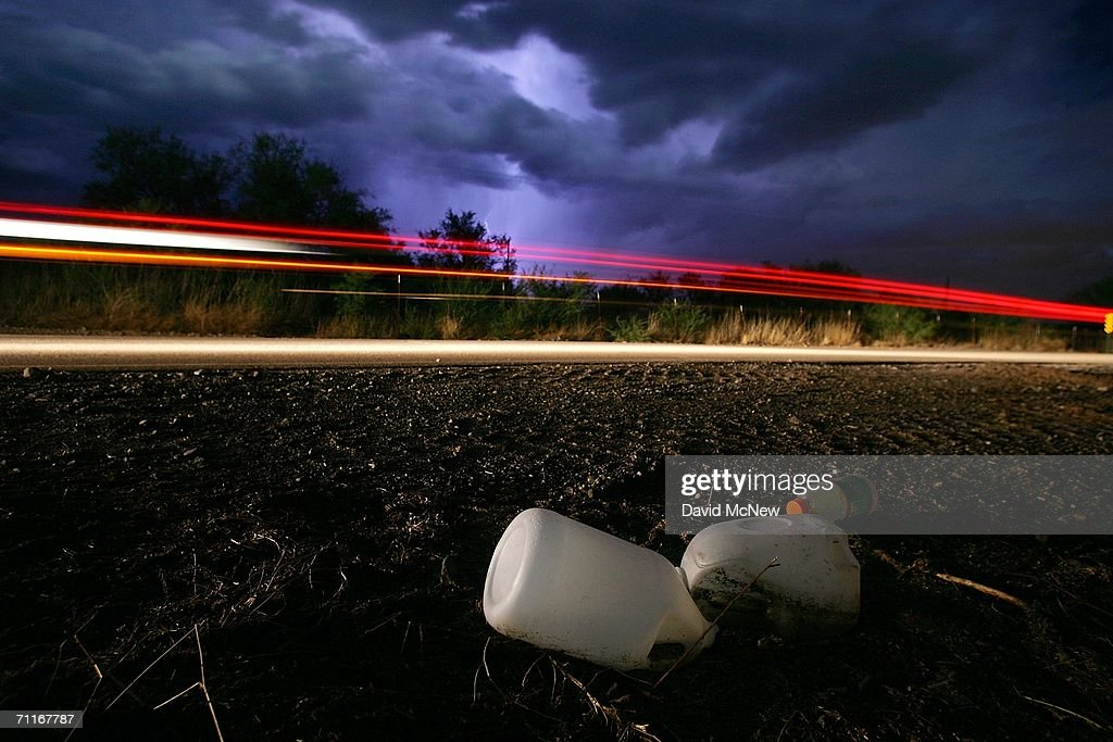Under a lightning-filled sky, a car passes water bottles likely discarded by illegal immigrants on the U.S. side of the U.S.-Mexico border on June 7, 2006 near Sasabe, Arizona, 60 miles north of Altar, Mexico. Many thousands of one gallon water bottles litter the desert north of the border as immigrants drop them during their trek. More illegal immigrants pass through Altar where immigrant smuggling is the primary industry, than any other town. Available services include 'coyotes' or guides, transportation over 60 miles or more of dirt road in vans carrying as many as 25 people, about 150 'hospedajes' or guest houses, provisions, a free mobile clinic catering mostly to people who were hurt trying to cross the border, and groups who warn immigrants on the dangers of the trek and help those in need. From here, most immigrants are guided through Sasabe, where nightly robberies have become an industry and rape is common, then across the US-Mexico border to walk for about 45 miles through the desert before being picked up by smuggler vehicles. It is during the walk that most of the 473 deaths of 2005 occurred, mostly from exposure to extreme heat and fatigue.