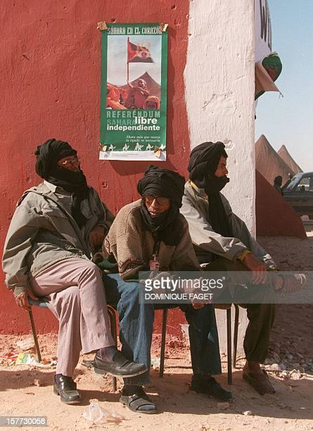 Under a poster for the referendum Sahrawi's refugee seat at Smara's camp 30 November in Tindouf Algeria A ceasefire in the conflict opposing the...