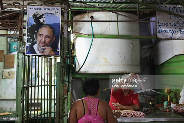 Under a poster of former Cuban President Fidel Castro a woman buys pork in an open air market in the Jesus Maria neighborhood of Habana Vieja January...