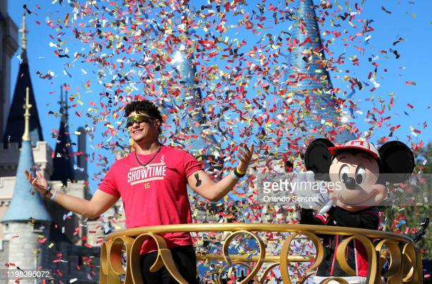 Under a shower of confetti, Kansas City Chiefs quarterback Patrick Mahomes responds to cheering fans with Mickey Mouse during a parade in the team's...