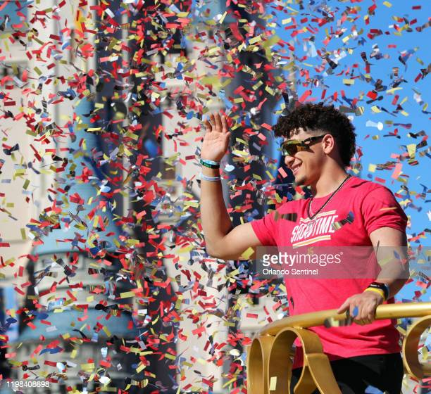 Under a shower of confetti Kansas City Chiefs quarterback Patrick Mahomes responds to cheering fans with Mickey Mouse during a parade in the team's...