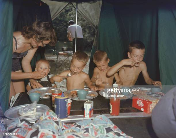Under a tent that extends over their station wagon the Baldwin family eats a meal from metal plates at a campsite in Yosemite Natioanl Park Caifornia...