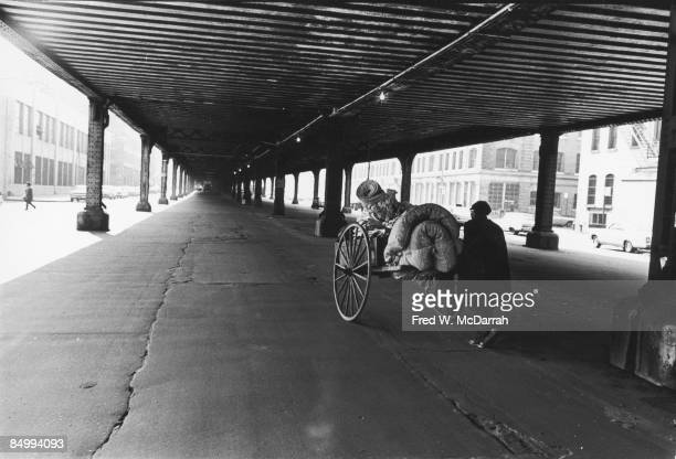 Under an elevated road an unidentified person pushes a cart with oversized spoked wheels and loaded with newspapers a folded mattress and other items...