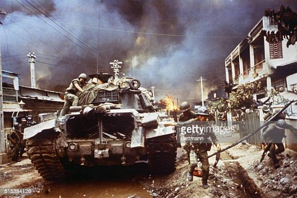 Under cover of tank Vietnamese rangers move up a street in Cholon as another part of the Chinese section of Saigon burns