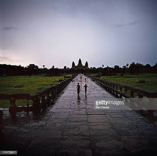 Under dark monsoon clouds children run to take cover from the rain at famous Angkor Wat in Cambodia probably the greatest archaeological site in the...