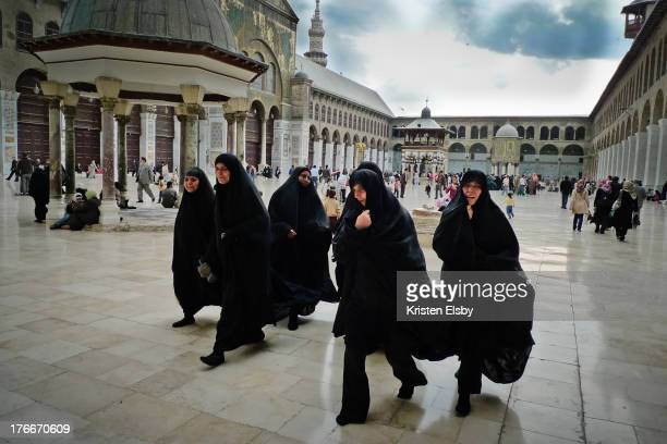 Under darkened skies, a group of women wearing black chadors walk together across the huge courtyard of Umayyad Mosque, one of the most sacred places...